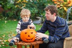 Young man and toddler boy making halloween pumpkin stock photos