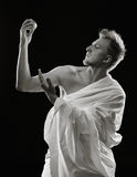 Young man and toga. Portrait, handsome young man sits in the studio - black and white image, dark background stock photography