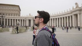 Young man from tokyo with backpack in Vatican city and St. Peter`s Basilica church, Rome, Italy. Travel tourist man. Outdoors during holidays in Europe. Slow stock footage