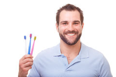 Young man with toothbrushes Stock Images