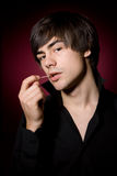 Young  man with toothpick in black shirt Stock Photo