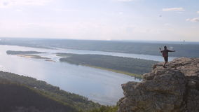 Young man on top of a mountain filming a panorama of the area and themselves. stock footage