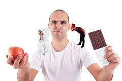 Young man torn between eating an apple and a choco. Late,between the devil and angel, on white Royalty Free Stock Photo