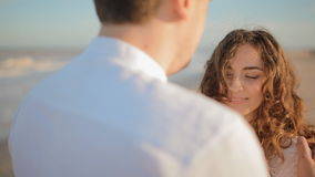 Young man touch face of his woman. Young caucasian couple on the seashore.Wind play in her hair.Woman look at her partner and smile.She likes his touch stock video