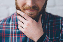 Young man touches with hand his beard Royalty Free Stock Photography