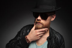 Young man touches his beard. Casual young man with his hand on his long beard, looking at the camera through his sunglasses . on a dark studio background stock images