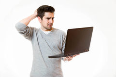 A young man touches his head wile working on his laptop Stock Photography