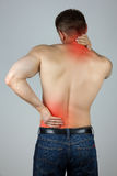 Young man touching his back and neck for the pain. Young man with back and neck pain in the red zone Stock Image