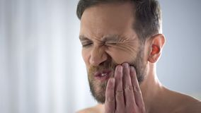 Young man touching his cheek, suffering from terrible toothache, sensitivity stock image