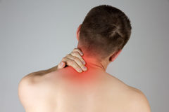 Young man touching his neck for the pain. Young man with neck pain in the red zone Stock Photography