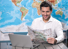 Young Man Tour Agency Concept. Young man tour agent sitting in office browsing laptop Stock Images