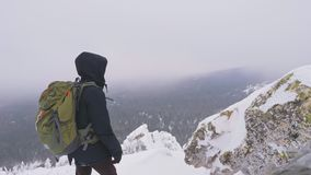 A young man with a backpack on his shoulders, stands on top of a snow-covered mountain and admires the landscape. A young man, a tourist, with a backpack on his stock video footage
