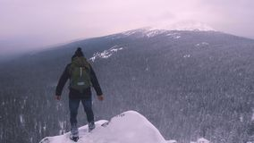 A young man, a tourist, stands on the edge of a snow-covered mountain and admires the top of the mountain. A young man, a tourist with a backpack, stands on the stock footage