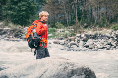 Young man tourist in mountain forest on the river bank Royalty Free Stock Images