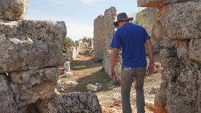 Young man tourist in panama exploring ancient city. Young man archaeologist in panama hat exploring ancient city Lyrboton in Turkey stock video footage