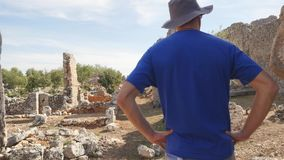 Young man tourist in panama exploring ancient city. Young man archaeologist in panama hat exploring ancient city Lyrboton in Turkey stock video