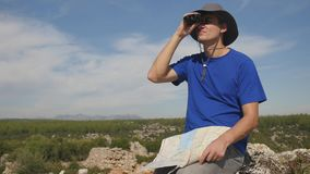Young man traveler with map looking far away through binoculars. Young man tourist in panama hat with map looking far away through binoculars sitting on ancinet stock footage