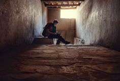 Young man tourist sits with laptop in old tibetan palace Royalty Free Stock Image