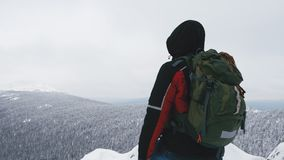 A young man, a tourist, stands on the edge of a snow-covered mountain and admires the top of the mountain. A young man, a tourist with a backpack, stands on the stock video