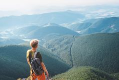 Young man tourist stands on the top of hill and enjoys with infinity hills panorama royalty free stock images