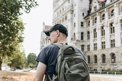 A young man or tourist or student with a backpack looks at the sights in Leipzig in Germany.  stock image