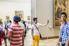 Young man tourist takes selfie in gallery in the Louvre Stock Image