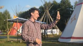 Young man tourist talking on the phone and smiling on the background teepee / tipi- native indian house. Man in hat traveler in su stock video footage