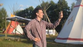 Young man tourist talking on the phone and smiling on the background teepee / tipi- native indian house. Man in hat traveler in su stock footage