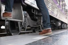 Young man, tourist or traveler stepping up to the train on railw. Feet of young man, tourist or traveler stepping up to the train on railway at train station Stock Images