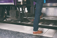 Young man, tourist or traveler stepping up to the train on railw. Feet of young man, tourist or traveler stepping up to the train on railway at train station Royalty Free Stock Photography