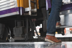 Young man, tourist or traveler stepping up to the train on railw. Feet of young man, tourist or traveler stepping up to the train on railway at train station Royalty Free Stock Image