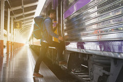 Young man, tourist or traveler stepping up to the train on railw. Feet of young man, tourist or traveler stepping up to the train on railway at train station Royalty Free Stock Photo