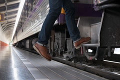 Young man, tourist or traveler stepping up to the train on railw. Feet of young man, tourist or traveler stepping up to the train on railway at train station Royalty Free Stock Images