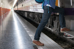 Young man, tourist or traveler stepping up to the train on railw. Feet of young man, tourist or traveler stepping up to the train on railway at train station Stock Photography