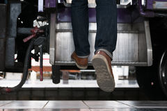 Young man, tourist or traveler stepping up to the train on railw. Feet of young man, tourist or traveler stepping up to the train on railway at train station Stock Image