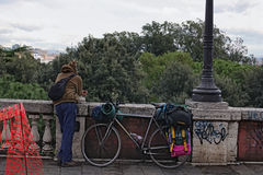 Young man tourist travels on bicycle. He looks at the landscape of the city. Campania, Italy.  Stock Photos