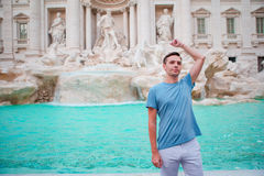 Young man tourist trowing coins at Trevi Fountain, Rome, Italy for good luck. Caucasian guy making a wish to come back. Stock Photography