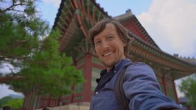 Young man tourist visits an ancient palace in Seoul, South Korea. Travel to Korea concept. Slowmotion shot