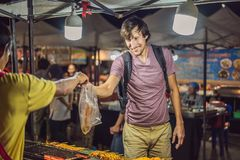 Young man tourist on Walking street Asian food market royalty free stock images