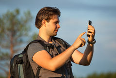 Young man tourist. Working with smartphone at travel outdoors. Searching route in navigator or making photos of location Royalty Free Stock Photography
