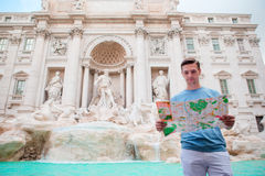 Young man with touristic citymap near Fountane di Trevi, Rome, Italy. Caucasian boy near fountain Fontana di Trevi with city map Royalty Free Stock Image