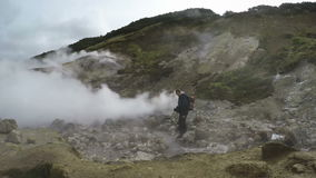 Young man tourists on thermal field watching at natural volcanic hot springs stock video footage