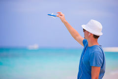 Young man with toy airplane enjoy music on beach vacation. Happy boy enjoy beach and warm weather while walking along. Young beautiful man relaxing at white sand Royalty Free Stock Image