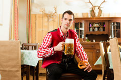 Young man in traditional Bavarian Tracht in restaurant or pub Stock Photos