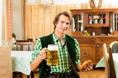 Young man in traditional Bavarian Tracht in restaurant or pub Stock Image