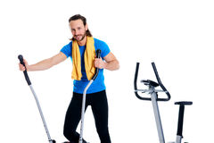 Young man train with fitness machine. Young man in blue shirt train with fitness machine and listening music stock photos