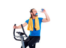 Young man train with fitness machine and drinking water. Young man in blue shirt train with fitness machine and drinking water royalty free stock photography