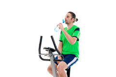 Young man train with fitness machine and drinking water Royalty Free Stock Photography