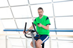 Young man train with fitness machine and listening music. Young man in green shirt train with fitness machine and listening music stock images