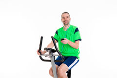 Young man train with fitness machine and listening music Royalty Free Stock Photography